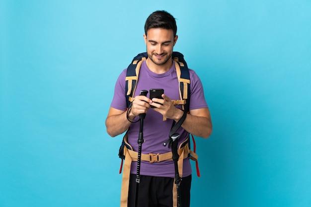 Joven caucásico con mochila y bastones de trekking aislado en azul enviando un mensaje con el móvil
