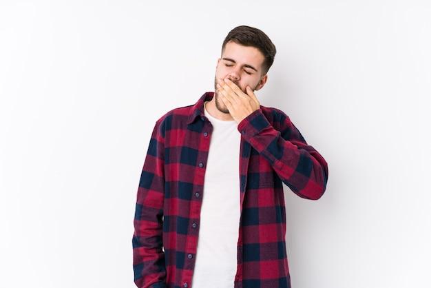 Joven caucásico posando en una superficie blanca aislado bostezando mostrando un gesto cansado cubriendo la boca con la mano.