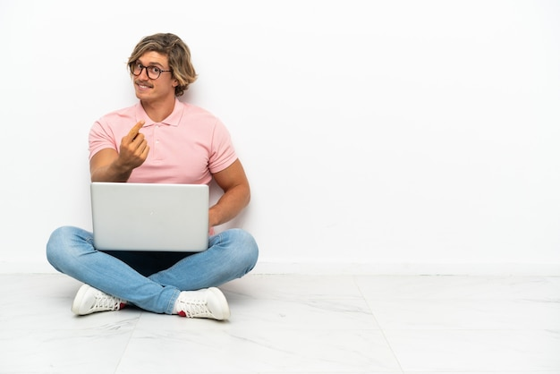 Joven caucásico sentado en el suelo con su portátil aislado