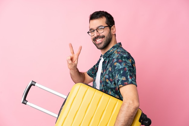 Joven caucásico sobre pared aislada en vacaciones con maleta de viaje y haciendo gesto de victoria
