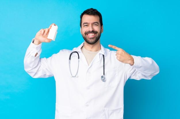 Joven caucásico sobre pared aislada vistiendo una bata de médico y sosteniendo pastillas