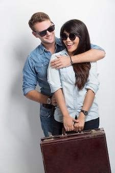 Joven caucásico sonriendo mientras le da a su novia asiática un abrazo