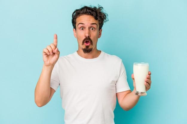 Joven caucásico sosteniendo un vaso de leche aislado sobre fondo azul con una gran idea, concepto de creatividad.