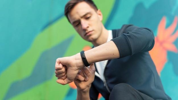 Joven caucásico está en su pulsera de fitness sobre fondo multicolor
