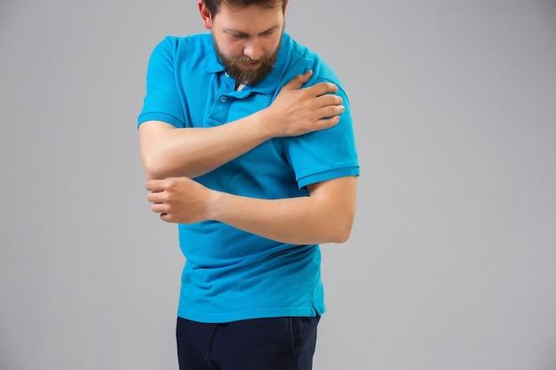 Joven caucásico sufre de dolor en el hombro