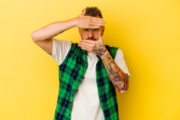 Joven caucásico tatuado aislado sobre fondo amarillo parpadea a la cámara a través de los dedos, avergonzado cubriendo la cara.