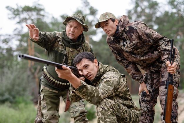 Joven cazador apuntando con escopeta de doble cañón.