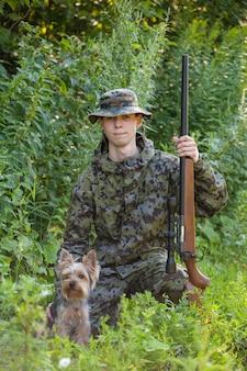 Joven cazador con pistola y yorkshire terrier cazando en el bosque.