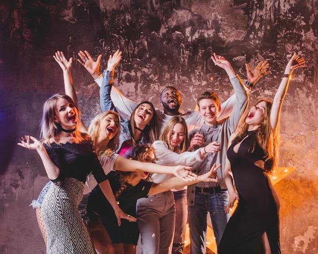 Joven celebrando amigos con las manos arriba