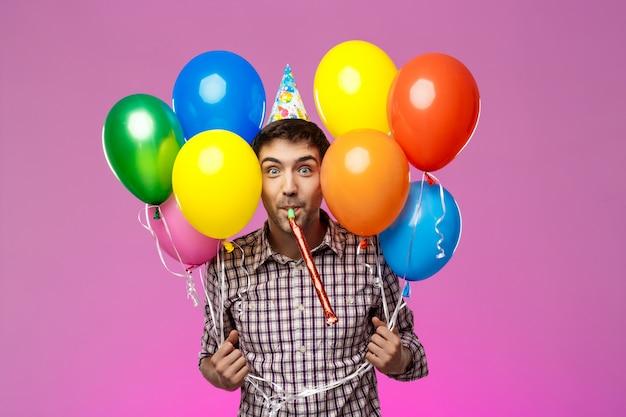 Joven celebrando cumpleaños, sosteniendo globos de colores sobre la pared púrpura.
