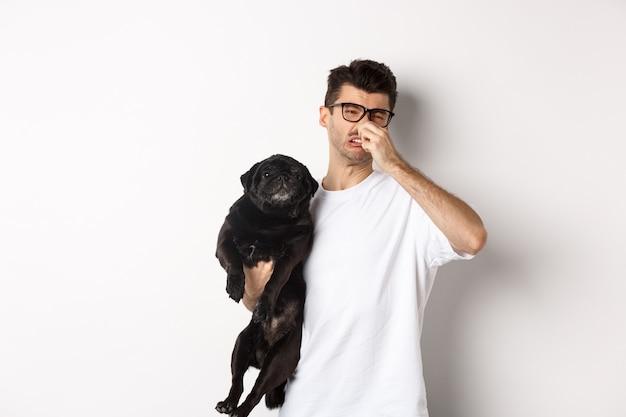 Joven cerró la nariz como sosteniendo pug, disgustado con mal olor pedo de animal, de pie sobre blanco