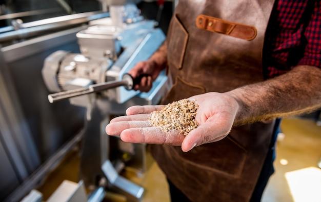 Un joven cervecero con un delantal de cuero controla la molienda de semillas de malta en un molino en una cervecería moderna