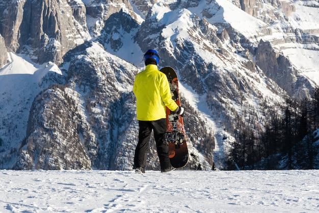 Un joven con una chaqueta amarilla camina en una pista de esquí con una tabla de snowboard