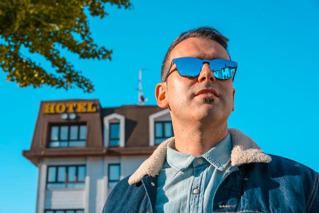 Joven en una chaqueta y gafas de sol al lado del hotel