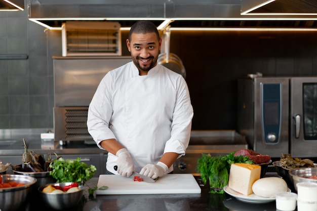 Joven chef africano de pie en la cocina profesional en el restaurante preparando una comida de carne