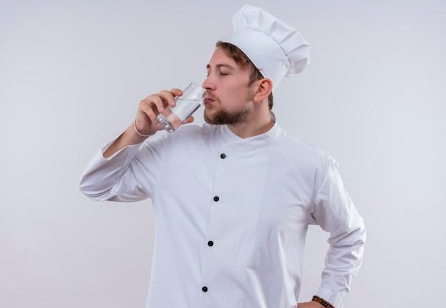 Un joven chef barbudo con uniforme de cocina blanco y sombrero bebiendo un vaso de agua mientras mira en una pared blanca