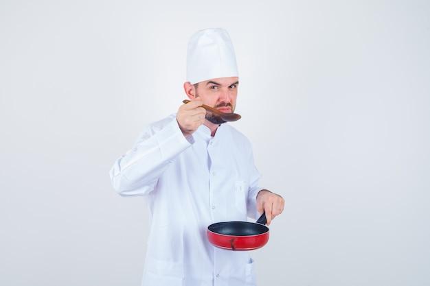 Joven chef degustación de comida con cuchara de madera en uniforme blanco y mirando curioso, vista frontal.