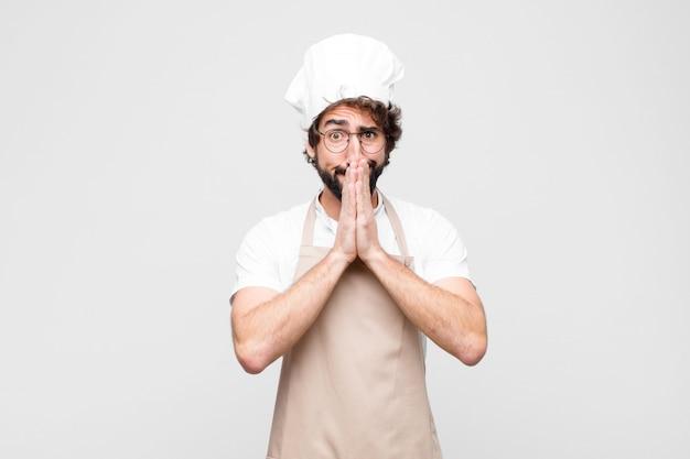 Joven chef loco que se siente preocupado, esperanzado y religioso, rezando fielmente con las palmas presionadas, pidiendo perdón contra la pared blanca