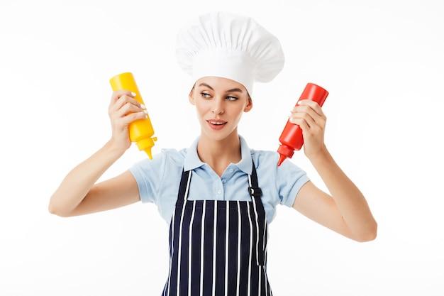 Joven chef mujer astuta en delantal a rayas y sombrero blanco soñando
