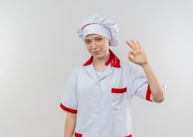 Joven chef mujer rubia complacida en uniforme de chef gestos ok signo de mano aislado en la pared blanca
