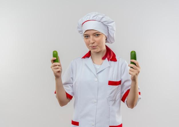 Joven chef mujer rubia complacida en uniforme de chef sostiene pepinos en dos manos aisladas en la pared blanca