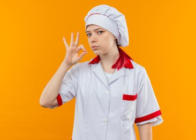Joven chef mujer rubia segura en uniforme de chef gestos ok signo de mano y parece aislado en la pared naranja