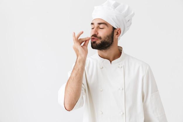 El joven chef positivo posando en uniforme hace un gesto delicioso y sabroso.