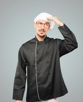 Joven chef preocupado haciendo un gesto de confusión