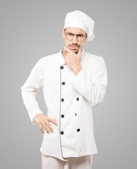 Joven chef preocupado haciendo un gesto de duda