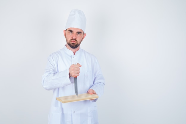 Joven chef sosteniendo una tabla de cortar y un cuchillo en uniforme blanco y mirando enojado, vista frontal.