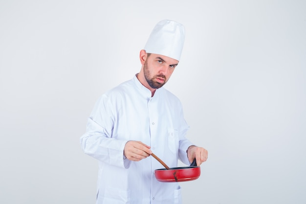 Joven chef en uniforme blanco mezclando comida con cuchara de madera y mirando pensativo, vista frontal.
