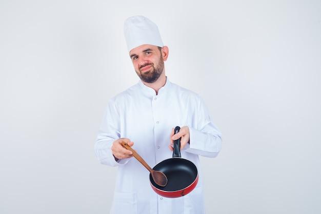 Joven chef en uniforme blanco mostrando una sartén vacía con cuchara de madera y mirando decepcionado, vista frontal.
