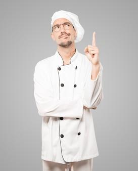 Joven chef vacilante apuntando hacia arriba con su dedo