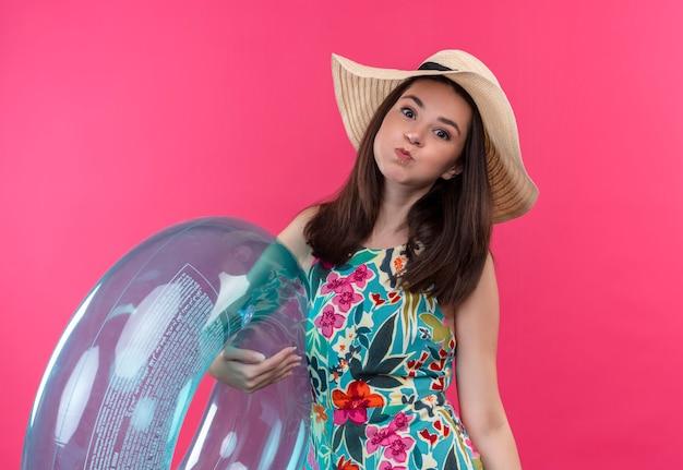 Joven chica caucásica con sombrero hinchando sus mejillas sosteniendo anillo de natación sobre fondo rosa aislado