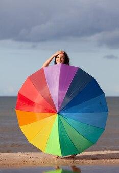 Joven chica desnuda posando con una sombrilla de colores en la playa en un día soleado con el fondo del cielo y el mar