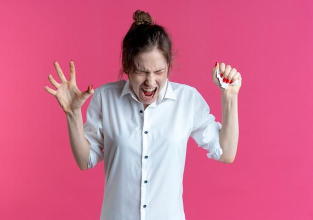Joven chica rusa rubia molesta presiona papel en la mano y aprieta otra mano aislada en el espacio rosa con espacio de copia