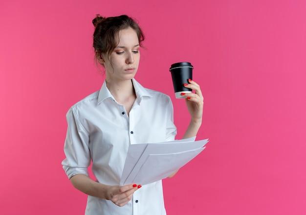 Joven chica rusa rubia segura mira hojas de papel sosteniendo la taza de café aislada en el espacio rosa con espacio de copia
