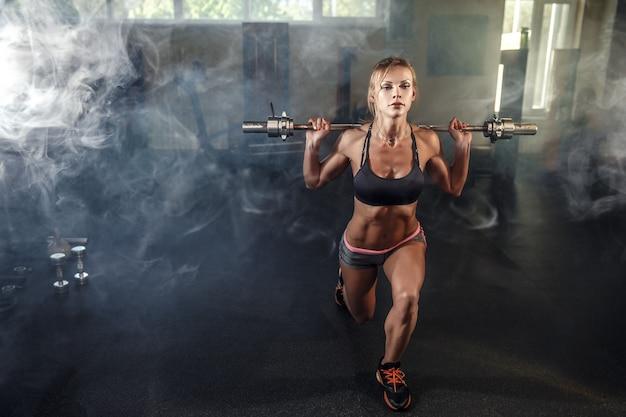 Joven chica sexy en el gimnasio haciendo sentadillas sobre fondo humo