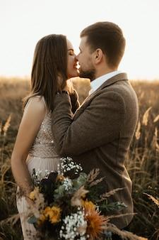 Joven chico y chica besan suavemente en la naturaleza