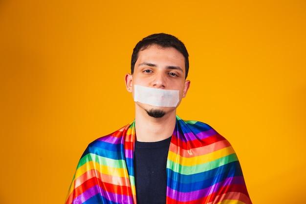 Joven chico homosexual con la boca cerrada en silencio por la violencia sufrida en la sociedad. prejuicio y violencia gay