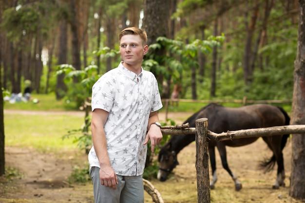 Joven chico rubio en un bosque de pinos cerca de un corral con un caballo