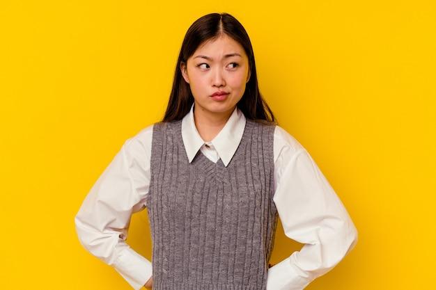 Joven china aislada sobre fondo amarillo confundida, se siente dudosa e insegura.