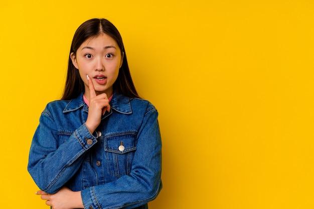Joven china aislada sobre fondo amarillo mirando hacia los lados con expresión dudosa y escéptica.