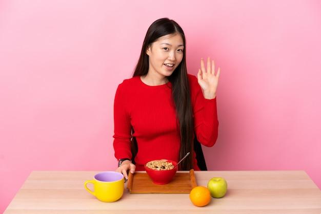 Joven china desayunando en una mesa saludando con la mano con expresión feliz
