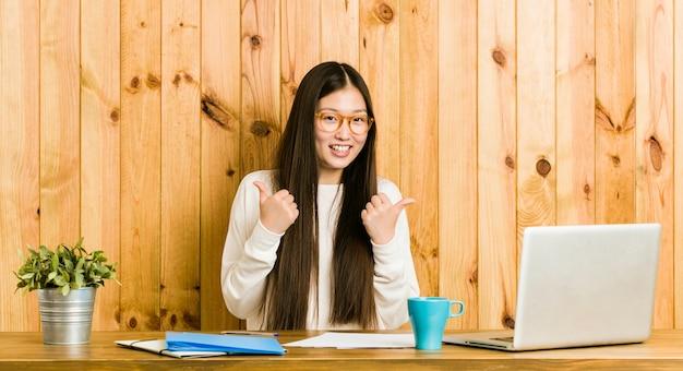 Joven china estudiando en su escritorio levantando ambos pulgares, sonriente y confiado