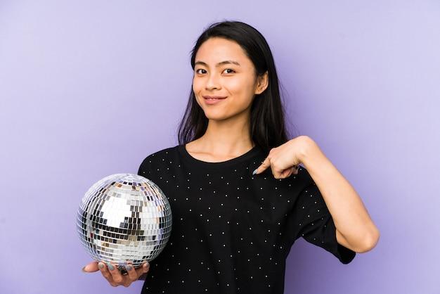 Joven china en una pared púrpura soñando con lograr objetivos y propósitos
