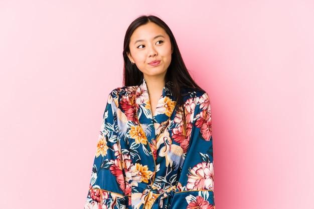 Joven china con un pijama de kimono aislado soñando con lograr objetivos y propósitos