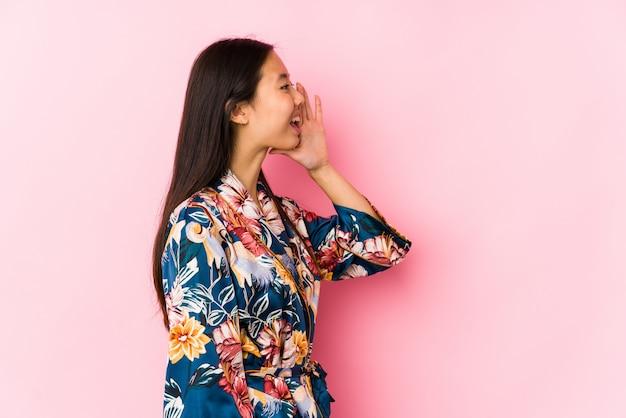 Joven china con un pijama de kimono gritando y sosteniendo la palma cerca de la boca abierta.