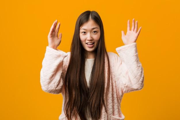 Joven china en pijama recibiendo una agradable sorpresa, emocionada y levantando las manos.