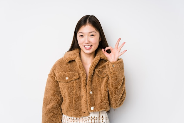 Joven china posando en una pared blanca guiña un ojo y tiene un gesto bien con la mano.